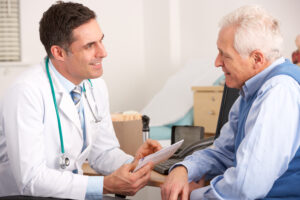 Old man talks with his doctor over medical paperwork.