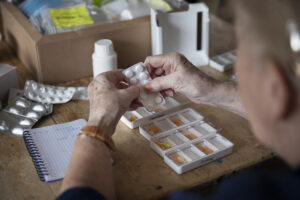 View of elderly woman putting pills into a weekly medication dispenser for mesothelioma pain