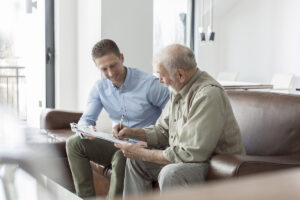Senior citizen discusses his benefits with a Medicare advisor on a sofa