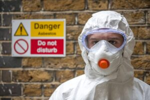 man in full body asbestos personal protective equipment with goggles and mask stands in front of danger sign