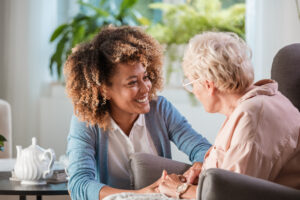 Smiling young female caregiver holds hands and talks with senior woman in living room