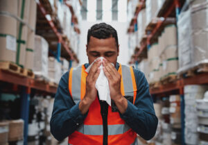Young black man working in warehouse blows his nose into a tissue.